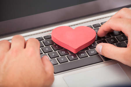 Foto de Cropped image of man dating online with heart shape on laptop - Imagen libre de derechos