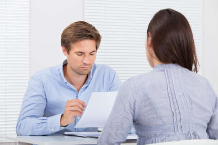 Mid adult businessman checking resume of female candidate during meeting in office