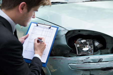 Photo pour Side view of writing on clipboard while insurance agent examining car after accident - image libre de droit