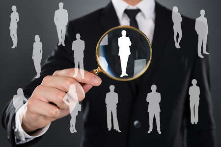 Midsection of businessman searching candidate with magnifying glass over gray background