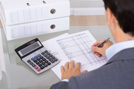 Business man accountant calculating invoices in office
