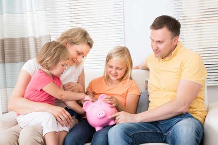 Family Saving Money In Piggybank At Home