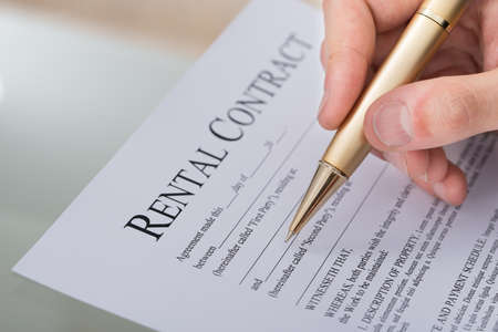 Cropped image of hand filling rental contract form on desk