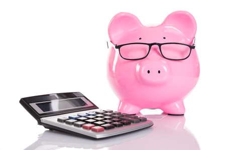 Piggybank and calculator. Isolated on white background