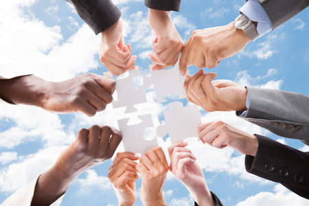 Photo for Directly below shot of multiethnic business people assembling jigsaw puzzle against sky - Royalty Free Image