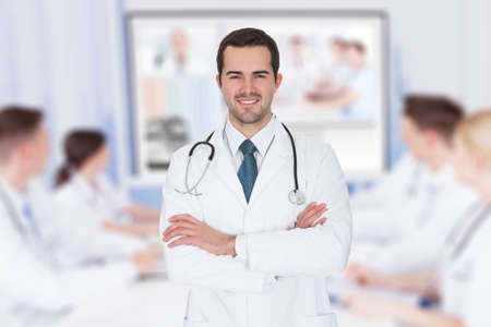 Photo for Portrait of young doctor with arms crossed against team video conferencing in meeting room - Royalty Free Image