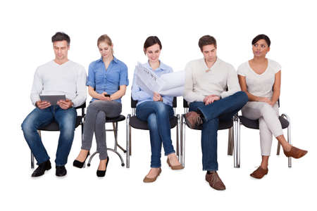 Full length of businesspeople doing various activities while sitting on chairs against white background