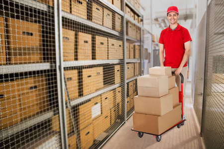 Portrait of happy delivery man pushing cart full of cardboard boxes in warehouse