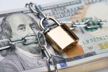 Photo pour Closeup of metallic chain and padlock around dollar bundle - image libre de droit