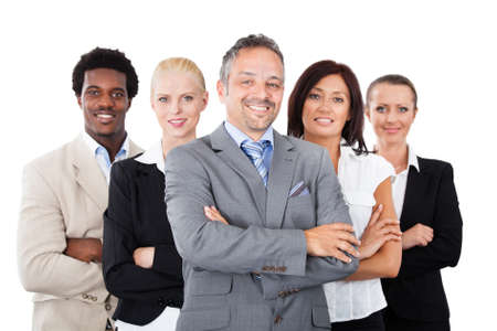 Portrait of confident businessman standing arms crossed with multiethnic team over white background