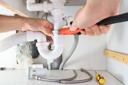 Photo for Close-up Of Male Plumber Fixing Sink In Bathroom - Royalty Free Image