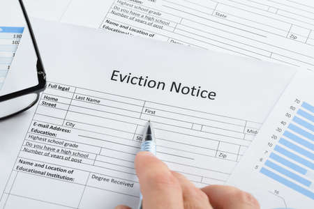 Close-up Of Hand With Pen And Eyeglasses Over Eviction Notice Paper