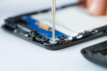 Photo pour Close-up Of Human Hand Repairing Cellphone With Screwdriver On Desk - image libre de droit