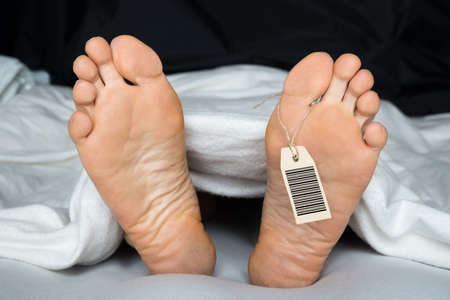 Photo for Deceased Person Covered In A Sheet With A Toe Tag - Royalty Free Image
