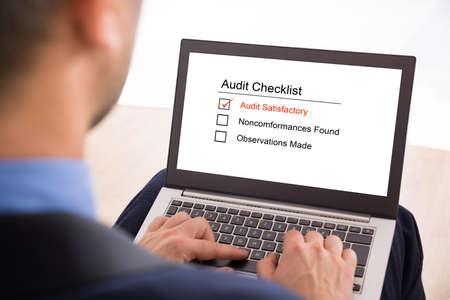 Close-up Of A Businessman Filling Audit Checklist Form On Laptop