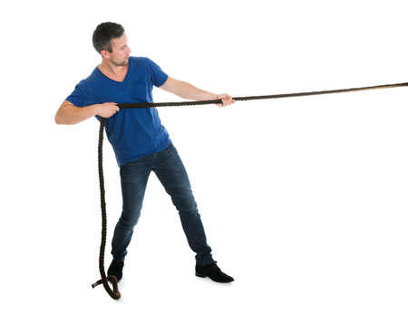 Portrait Of A Man Pulling Rope Over White Background