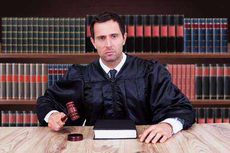 Portrait Of Serious Male Judge Striking Gavel In Courtroom