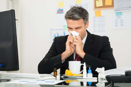 Mature Businessman At Office Desk Blowing His Nose