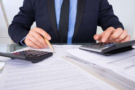 Photo pour Close-up Of Businessman Calculating Invoices Using Calculator - image libre de droit