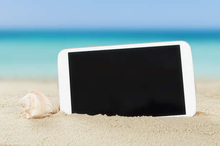 Closeup of tablet computer and shell on sand at beach