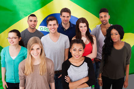 Happy Multi-ethnic Group Of People Standing In Front Of Brazil Flag
