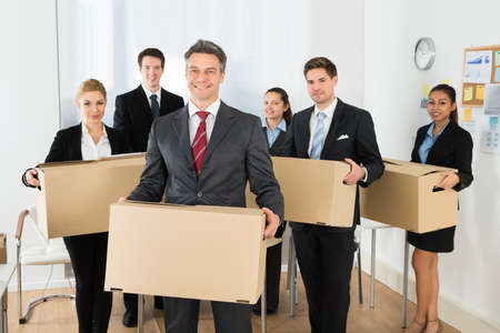 Photo pour Portrait Of Happy Multiethnic Employees In Office Holding Cardboard Boxes - image libre de droit