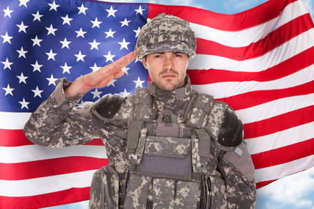 Foto per Portrait Of Soldier Saluting In Front Of American Flag - Immagine Royalty Free