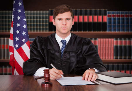 Portrait Of Young Male Judge Sitting In Courtroom