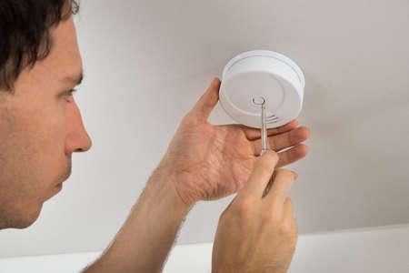 Photo pour Close-up Of Electrician With Screwdriver Repairing Fire Sensor - image libre de droit