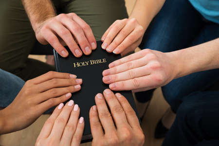 Foto de Group Of People Holding Holy Bible And Praying Together - Imagen libre de derechos