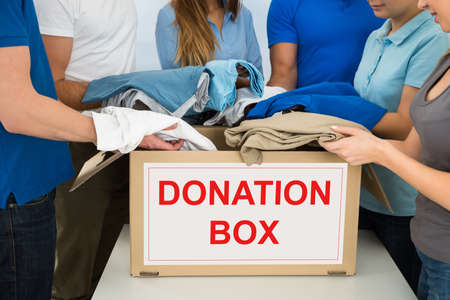 Close-up Of People Putting Clothes Inside Donation Box