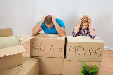 Photo pour Frustrated Young Couple With Moving Boxes At Home - image libre de droit