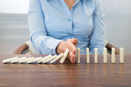 Photo for Close-up Of Businesswoman Stopping The Effect Of Domino With Hand At Desk - Royalty Free Image