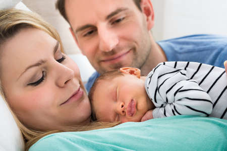 Photo pour Close-up Of Two Parents Looking At Newborn Sleeping Baby - image libre de droit