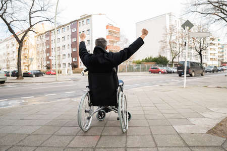 Rear View Of A Disabled Man On Wheelchair With Hand Raised