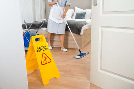 Photo for Female Maid Cleaning Floor In Hotel Room - Royalty Free Image