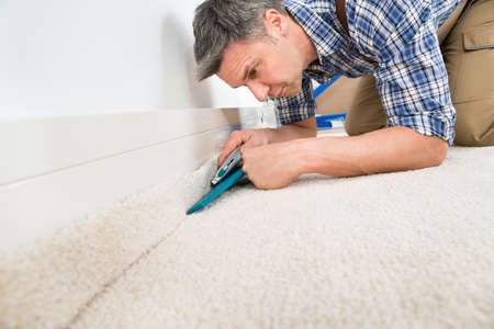 Close-up Of A Craftsman Fitting Carpet On Floor