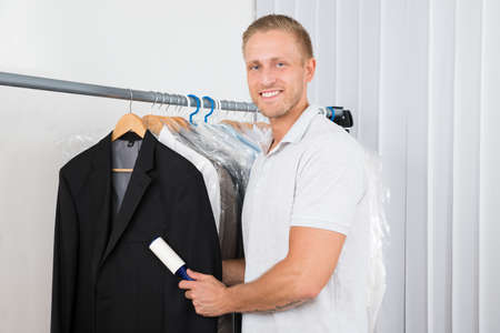 Young Happy Man Cleaning Dust With Lint Roller Of Coat In Clothes Store