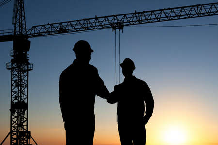 Photo pour Silhouette Of Two Architect At Construction Site Shaking Hand - image libre de droit