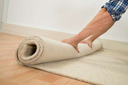 Close-up Of A Male Worker Folding Carpet On Floor At Home