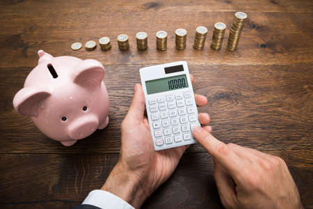 Businessman Using Calculator With Piggybank And Stack Of Coins On Desk