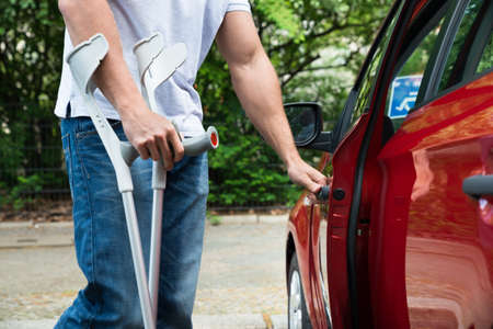 Close-up Of A Disabled Man With Crutches Opening Door Of A Car