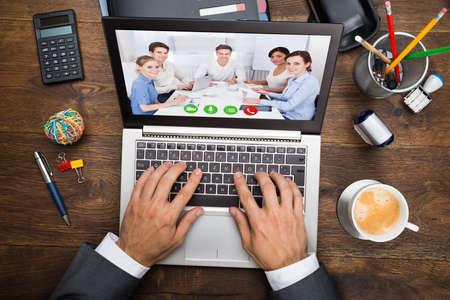 Photo pour Businessman In Video Chatting With His Colleagues On Laptop - image libre de droit