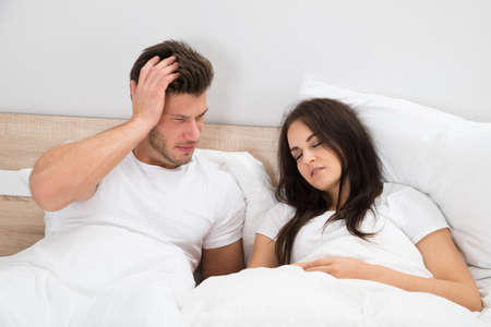 Upset Young Man Looking At Woman Snoring In Bed At Home