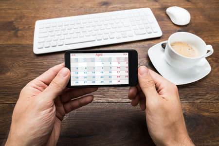 Close-up Of Person Hands With Mobile Phone Showing Calendar At Desk
