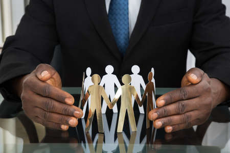 Close-up Of Businessman Hands Protecting Paper Cutout People At Desk