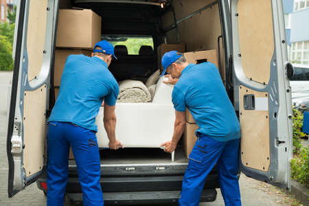 Photo pour Two Male Workers In Blue Uniform Adjusting Sofa In Truck - image libre de droit