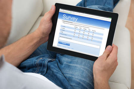 Photo pour Close-up Of Person On Sofa With Digital Tablet Showing Survey Form - image libre de droit