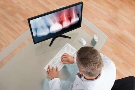 Foto de Young Male Dentist Looking At Teeth X-ray On Computer - Imagen libre de derechos