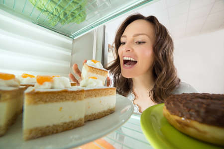 Photo pour Hungry Young Woman Eating Slice Of Cake From Fridge At Home - image libre de droit